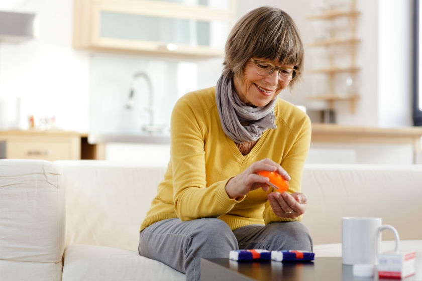 Woman sitting on couch places pills into a pill counter.