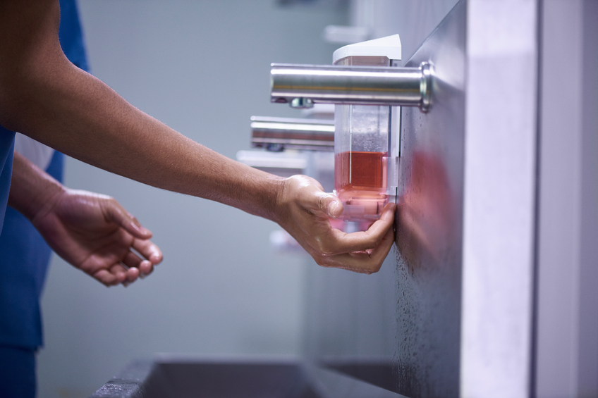 People in medical scrubs wash their hands.